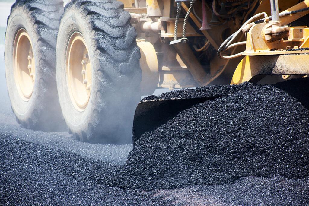 Asphalt truck laying asphalt.
